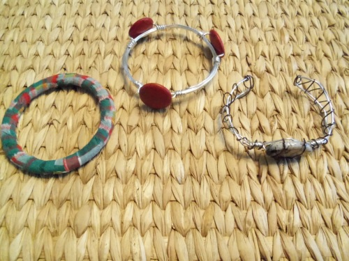 Here is an assortment of bracelets. One is wrapped in fabric strips and the other two are made from wire and beads.