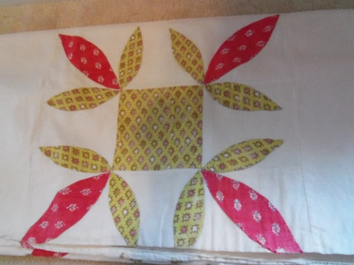 Here is a red and green star-patterned quilt. It is small and is only a quilt top since it was never completed.